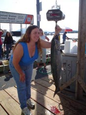 59th Golden North Salmon Derby winner Debbie White checks the official scale with her 32.9 pound king salmon on the hook.